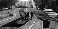 1906 photo of street and trolley tracks ripped by quake